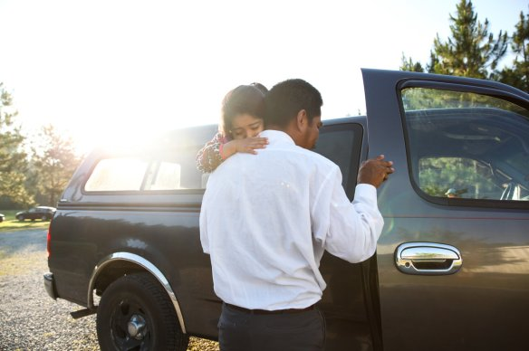 Farmworker Benito carrying his daughter. Photo credit: Morgan McCloy, NPR