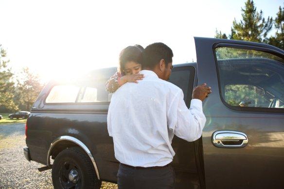 Farmworker Benito carrying his daughter. Photo credit: Morgan McCloy, NPR