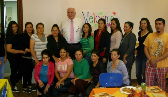 Representative Kelly (center) poses next to Leonor Saldaña (left of the Rep. Kelly), president of the Policy Committee, and the center's farmworker parents during his visit.